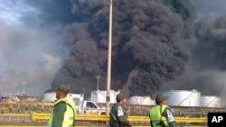 Những người lính bảo vệ quốc gia đứng nhìn đám khói lớn bốc lên từ nhà máy lọc dầu Amuay, gần Punto Fijo, Venezuela, vào thứ Bảy, 25 tháng Tám, 2012