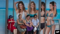 FILE - Four women wait at a bus stop in front of an advertising poster for swimwear and beach wear in Madrid, Spain, May 27, 2017. The head of the U.N. for Women is urging advertisers to eliminate such stereotypes in their ads.