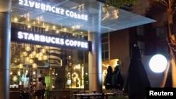 Nhân viên chuẩn bị mở cửa hàng cà phê Starbucks ở TP HCM.