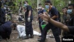 Polisi Malaysia dan pakar forensik menggali kuburan di Bukit Wang Burma di Malaysia utara dekat perbatasan Thailand, di mana ditemukan 139 jasad manusia (26/5).