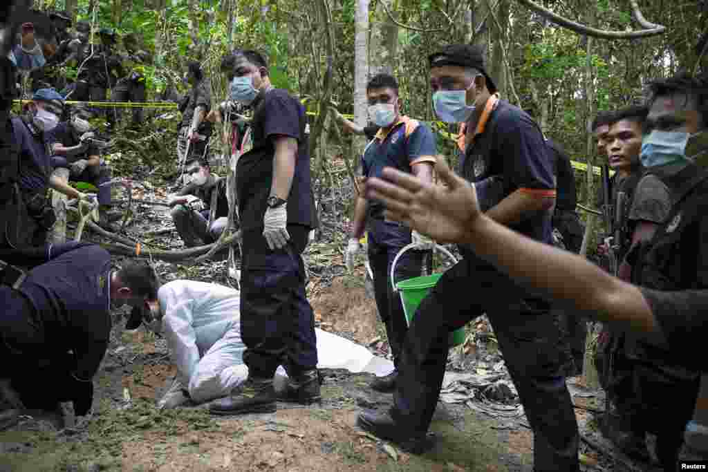 Forensic experts dig out human remains near the abandoned human trafficking camp in the jungle close to the Thailand border at Bukit Wang, Burma, in northern Malaysia, May 26, 2015.