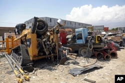 FILE - In this May 3, 2021 file photo, a man rests in the shade of destroyed machinery sold by the US military to a scrapyard, outside Bagram Air Base, in Afghanistan. (AP Photo/Rahmat Gul, File)