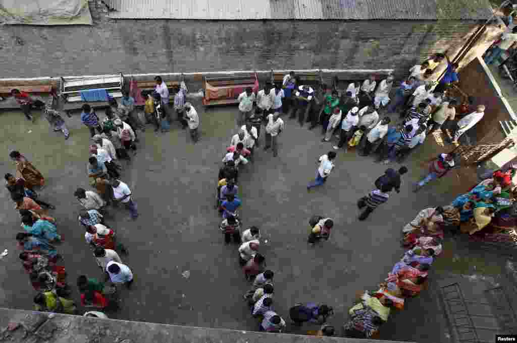 Voters line up to cast their votes outside a polling station at Howrah district in the eastern Indian state of West Bengal, April 30, 2014.