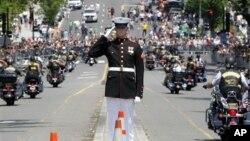 Seorang perwira Angkatan Laut memberikan penghormatan kepada para pengendara sepeda motor yang melintas di jalan saat parade tahunan 'Rolling Thunder' memperingati Memorial Day di Washington (27/5).