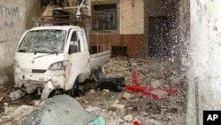 Nước phun tung tóe từ một ống nước bị vỡ bên cạnh chiếc xe hơi bị hư hại, trong thành phố Homs 30/3/12