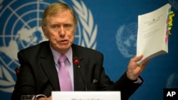 Michael Kirby, chairperson of the commission of Inquiry on Human Rights in the Democratic People's Republic of Korea, shows the commission's report during a press conference at the United Nations in Geneva, Switzerland, Feb. 17, 2014.