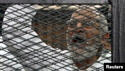 Muslim Brotherhood leader Mohammed Badie shouts slogans from the defendant's cage during his trial with other leaders of Brotherhood in a courtroom in Cairo, Dec. 11, 2013.
