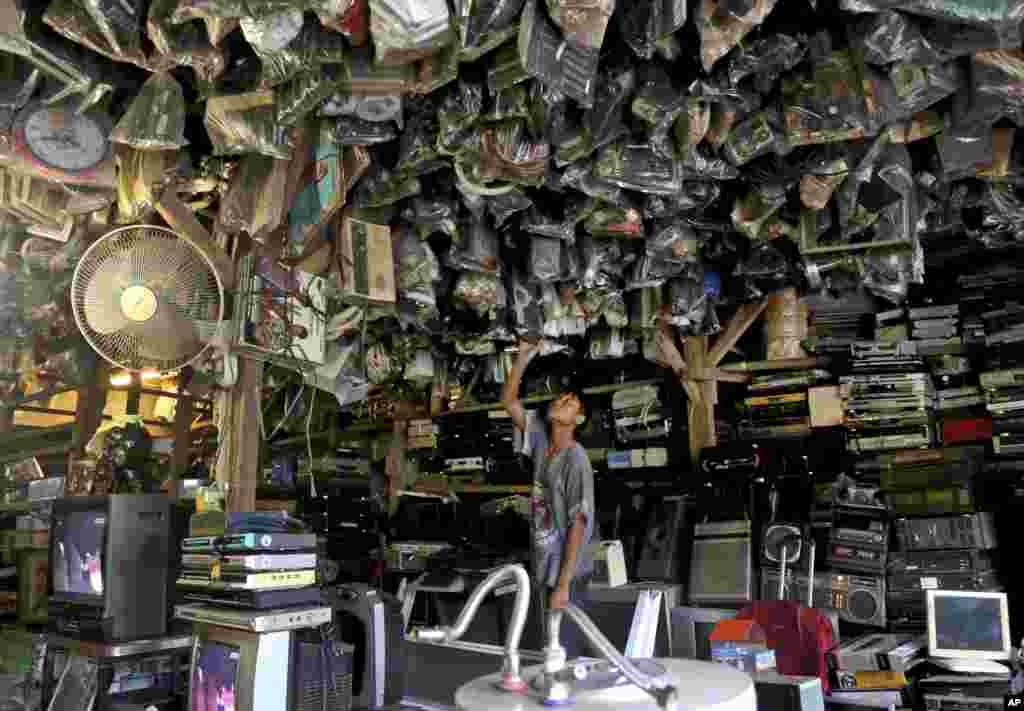 A customer browses through used items at a flea market on the outskirts of Jakarta, Indonesia.