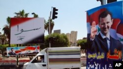 A vehicle drives past campaign posters of the June 3 presidential election in Damascus, Syria, May 12, 2014.