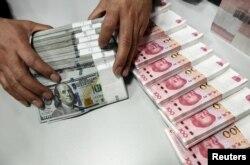 중국 산시성 타이위안의 은행에서 직원이 달러와 위안을 세고 있다. (자료사진)