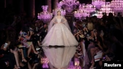 A model presents a wedding dress creation by Lebanese designer Elie Saab as part of his Haute Couture Fall/Winter 2014-2015 fashion show in Paris July 9, 2014.