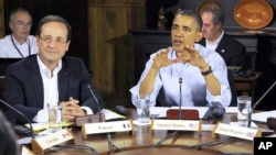 French President Francois Hollande, left, listens as U.S. President Barack Obama speaks at the start of the first working session of the G8 Summit at Camp David, Md., May 19, 2012.