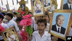 Pelajar di Kamboja memegang potret mantan Raja Norodom Sihanouk (kanan), putranya Raja Norodom Sihamoni, dan bunga dalam sebuah perayaan hari kemerdekaan di Phnom Penh.