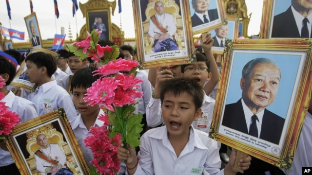 Cambodian students hold portraits of former King Norodom Sihanouk during an Independence Day celebration in Phnom Penh, Cambodia, Nov. 9, 2011.