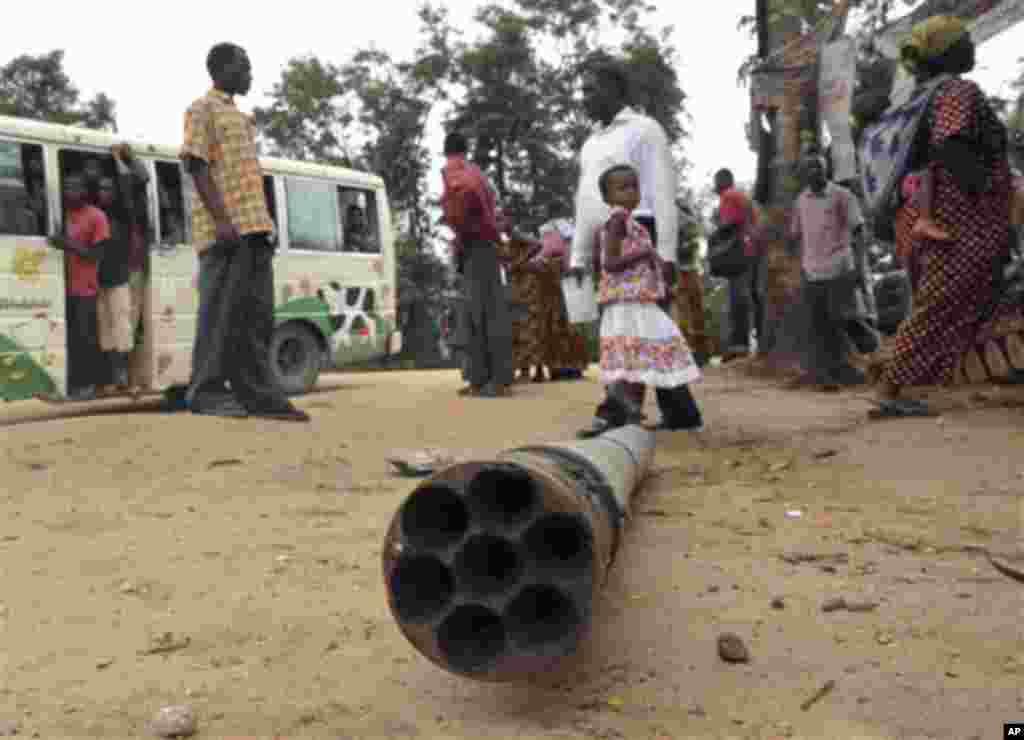 Watu wakitizama mabaki ya mziga uloripuka kewnye barabara ya Pugu-Malohe nje ya Dar es Salaam Alhamisi Feb 17, 2011