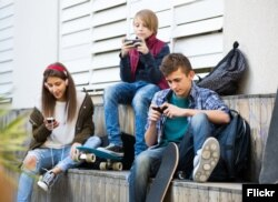 FILE -- Young people using smartphones. (Photo courtesy Kuvituskuvat via Flickr)