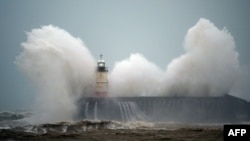 Waves crash over Newhaven Lighthouse on the south coast of England on February 9, 2020, as Storm Ciara swept over the country.