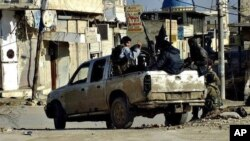 FILE - This undated file image posted on a militant website Jan. 14, 2014, shows fighters from the al-Qaida linked Islamic State of Iraq and the Levant (ISIL) patrolling in Raqqa, Syria.