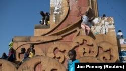 Crianças brincam num monumento de Bissau, capital da Guiné-Bissau.