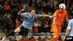 Arjen Robben của Hà Lan, mặt, dùng đầu ghi bàn thắng thứ 3 vì Diego Godin của Uruguay, trái, không cản được anh.