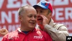 Pemimpin Partai Sosialis Venezuela Diosdado Cabello, kiri, mendengarkan bisikan Wakil Presiden Venezuela Tareck El Aissami saat protes menentang AS di Caracas, Venezuela, 28 Maret 2017.