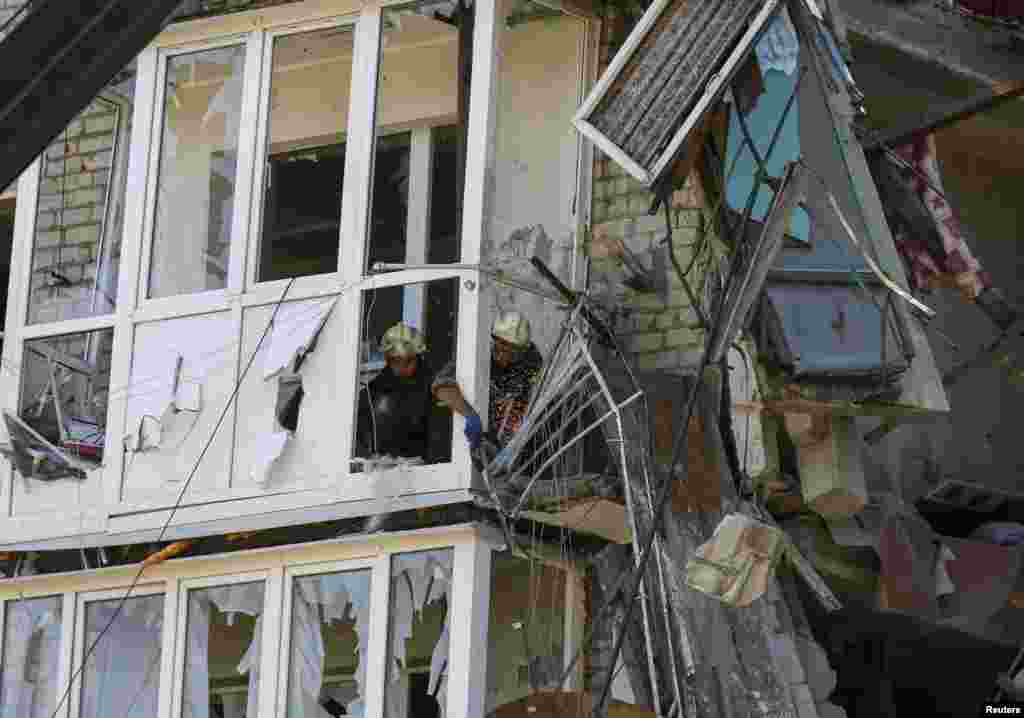 Rescuers remove damaged materials from a shattered five-story building that was damaged by a recent shelling, near the eastern Ukrainian town of Slovyansk, July 16, 2014.