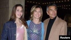 Olivia Newton-John (centro) con su hija Chloe y Patrick McDermott. Foto de archivo 2001. McDermott desapareció en 2005 durante un viaje de pesca. En 2008 fue declarado oficialmente muerto. Ahora ha sido descubierto viviendo en Nayarit, México.