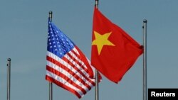 FILE - The U.S. flag flutters next to the Vietnamese flag during a welcoming ceremony for the U.S. defense secretary in Hanoi, Vietnam June 1, 2015. Vietnam has advocated for relaxation of the arms embargo to reflect a greater level of trust with the U.S.