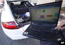 Stanford graduate student Mick Kritayakirana uses a laptop computer as he demonstrates the computer system inside a driverless car on the Stanford University campus in Palo Alto, Calif.