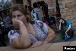 FILE - Melanie Starnauld and her 19-year-old son Mathew, who lost their home to Hurricane Harvey, await to be evacuated from Rockport, Texas, Aug. 26, 2017.
