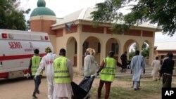 Des secouristes ramassent un corps après un attentat suicide contre un camp de personnes déplacées à Maiduguri, au Nigeria, lundi 24 juillet 2017.