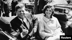 Former United States President John F. Kennedy and first lady Jackie Kennedy sit in a car in front of Blair House during the arrival ceremonies for Habib Bourguiba, president of Tunisia, in Washington, in this handout image taken on May 3, 1961.