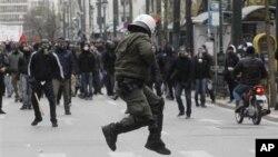 Một cảnh sát chống bạo loạn Hy Lạp cố tránh đá của người biểu tình ném vào ông. Dân Hy Lạp xuống đường phản đối biện pháp thắt lưng buộc bụng
