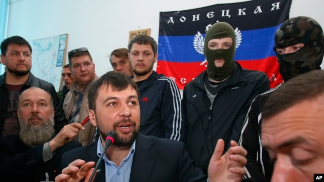 Denis Pushilin, foreground center, spokesman of the self-appointed Donetsk People's Republic, speaks to reporters inside the regional administration building seized earlier in Donetsk, Ukraine, April 18, 2014.