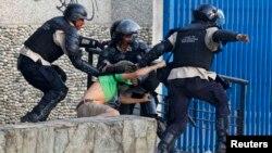 Policías venezolanos capturan a un manifestante en Caracas.