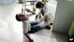 Nạn nhân nhiễm chất da cam Lê Văn Tâm, 14 tuổi, được cha săn sóc tại trung tâm phục hồi chức năng ở Đà Nẵng, Việt Nam