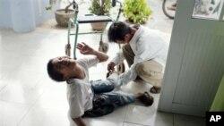 На оваа фотографија, направена на 8-ми август 2012-та, таткото ја подига 14-годишната Ле Ван Там во рехабилитационен центар во Дананг, Виетнам. Децата се раѓаат со физички или ментални недостатоци, за кои директорот на центарот вели дека ги причинува исзложеноста на нивните родители на хемикалијата диоксин во хербицидот Портокаловиот агенс. (AP Photo/Maika Elan)