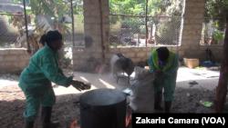 Mariam et l'une de ses employées mettent les plastiques dans la cuve, à Conakry, le 5 février 2019. (VOA/Zakaria Camara)