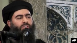 This file image made from video posted on a militant website in July 2014, which has been authenticated based on its contents and other AP reporting, purports to show Abu Bakr al-Baghdadi, the leader of the Islamic State group, delivering a sermon at a mosque in Mosul, Iraq.