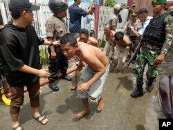 Petugas polisi dan tentara mengawasi narapidana yang dievakuasi dari Penjara Kabanjahe di Kabanjahe, Sumatra Utara, Rabu, 12 Februari 2020.