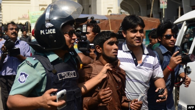 Bangladeshi police detain a suspected Jamaat-e-Islami activist in front of the Baitul Mukarram, the national mosque in Dhaka, March 1, 2013.