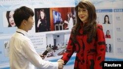 """Một người đàn ông bắt tay với robot có tên là """"Dương Dương"""" tại Hội thảo Internet Di động Toàn cầu ở Bắc Kinh, Trung Quốc, ngày 29/4/2016."""