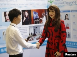 "FILE - A man shakes hands with a humanoid robot named ""Yangyang"" showing a facial expression, during its demonstration at the Global Mobile Internet Conference (GMIC) 2015 in Beijing, China, April 29, 2015."