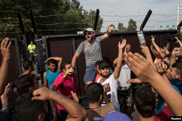 Migrants shout to open the border near the village of Horgos, Serbia, Sept. 15, 2015.