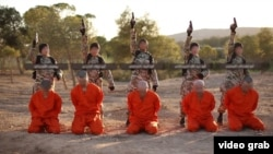 FILE - A screenshot from an Islamic State propaganda video purports to show young boys executing a group of captives.