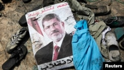 A poster of deposed Egyptian president Mohamed Morsi lies amid debris in a cleared protest camp of his supporters in Cairo August 15, 2013.