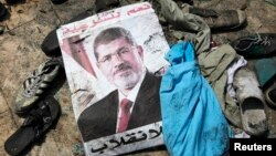 A poster of deposed Egyptian president Mohamed Morsi lies amid debris of a cleared protest camp of his supporters in Cairo, Aug. 15, 2013.
