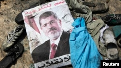A poster of deposed Egyptian president Mohamed Morsi lies amid debris of a cleared protest camp of his supporters in Cairo August 15, 2013.