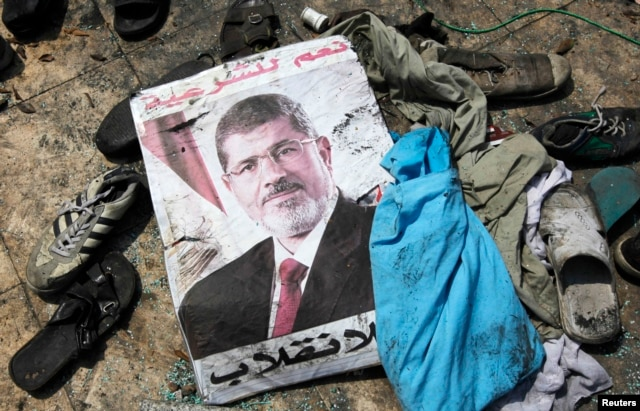 A poster of deposed Egyptian president Mohamed Morsi lies amid debris of a cleared protest camp of his supporters in Cairo Aug. 15, 2013.