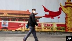 湖北武汉一名居民走过街头一幅北京天安门的招贴画。